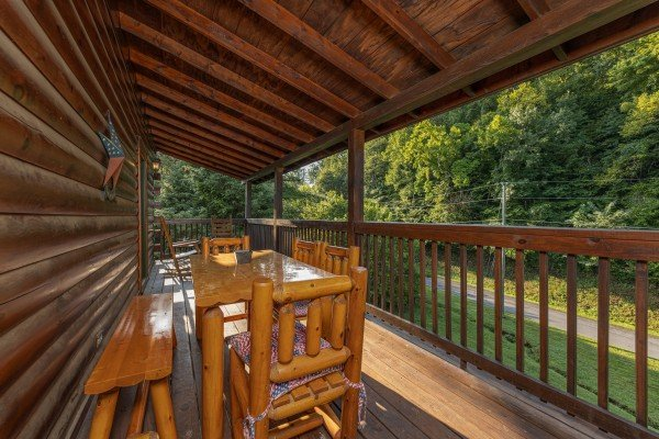Outdoor dining space on a covered deck at Family Getaway, a 4 bedroom cabin rental located in Pigeon Forge