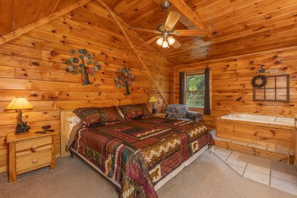 King bed, two night stands, two lamps, and a jacuzzi at Family Getaway, a 4 bedroom cabin rental located in Pigeon Forge