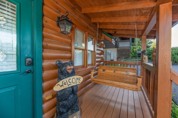 Swing and custom welcome sign on a covered front porch at Southern Charm, a 2 bedroom cabin rental located in Pigeon Forge