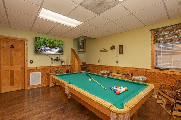 Pool table and TV in the game room at Southern Charm, a 2 bedroom cabin rental located in Pigeon Forge