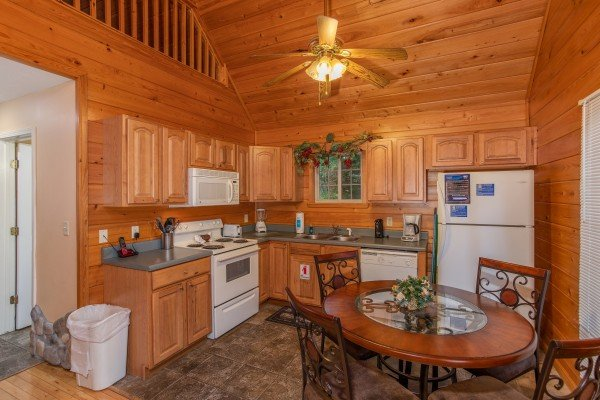 Kitchen with a dining table for four and white appliances at Eastern Retreat, a 1-bedroom cabin rental located in Gatlinburg