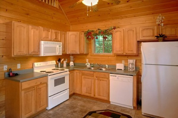 Kitchen with white appliances at Eastern Retreat, a 1-bedroom cabin rental located in Gatlinburg