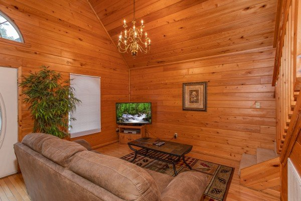 Living room with a sofa, television, and vaulted ceiling at Eastern Retreat, a 1-bedroom cabin rental located in Gatlinburg