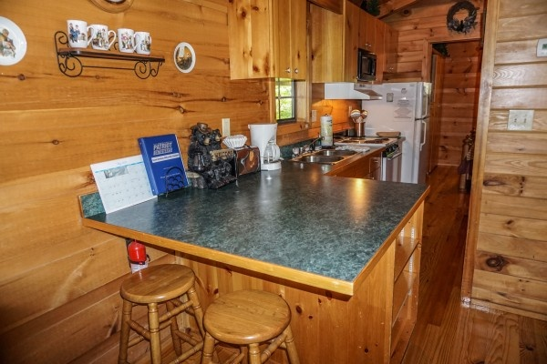breakfast bar for two in the kitchen at seclusion a 1 bedroom cabin rental located in gatlinburg