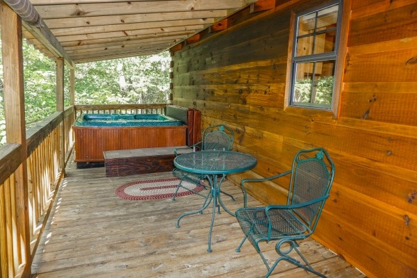 patio table and chairs on the deck at seclusion a 1 bedroom cabin rental located in gatlinburg