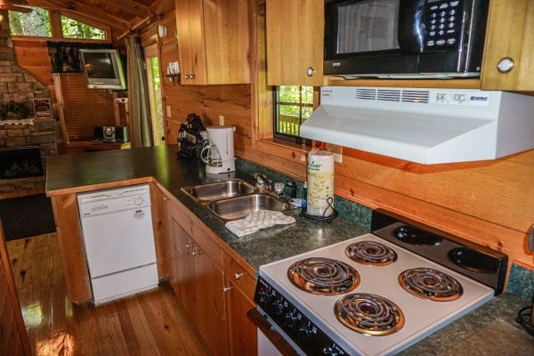 kitchen with white appliances at seclusion a 1 bedroom cabin rental located in gatlinburg