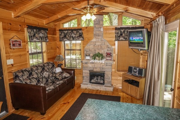 living room with stone fireplace at seclusion a 1 bedroom cabin rental located in gatlinburg