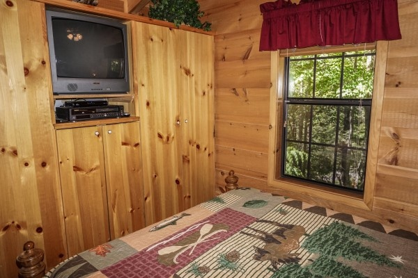 TV in the wall at foot of bed at Seclusion, a 1 bedroom cabin rental located in Gatlinburg