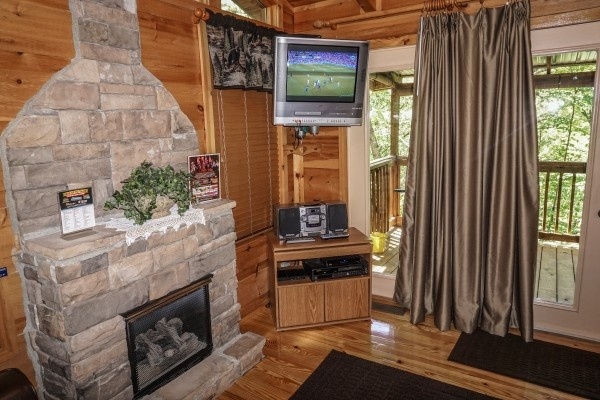 TV mounted in the corner of the living room at Seclusion, a 1 bedroom cabin rental located in Gatlinburg