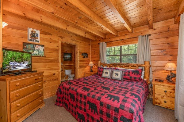 Bedroom with king bed, log furniture, dresser, and TV at Away From it All, a 1 bedroom cabin rental located in Pigeon Forge
