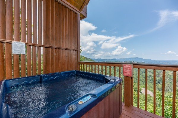 Hot tub and privacy fence on a deck at Away From it All, a 1 bedroom cabin rental located in Pigeon Forge