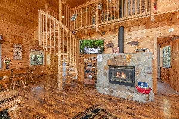 Living room with fireplace, TV, and spiral staircase at Away From it All, a 1 bedroom cabin rental located in Pigeon Forge