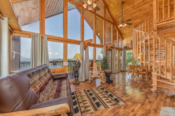 Living room with large windows, vaulted ceiling, and spiral staircase at Away From it All, a 1 bedroom cabin rental located in Pigeon Forge