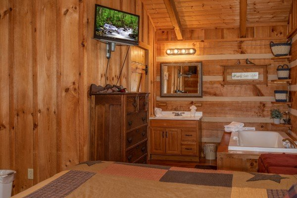 Jacuzzi, bathroom vanity, TV, and dresser in the bedroom at Blue Mountain Views, a 1 bedroom cabin rental located in  Pigeon Forge