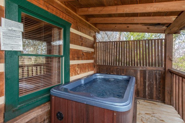 Hot tub with privacy fence on a covered deck at Blue Mountain Views, a 1 bedroom cabin rental located in  Pigeon Forge