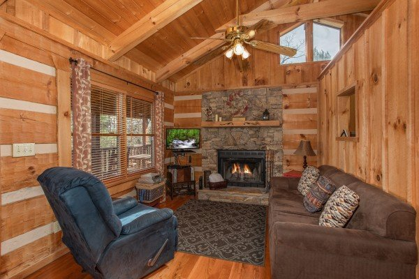 Fireplace, TV, recliner, and sofa in the living room at Blue Mountain Views, a 1 bedroom cabin rental located in  Pigeon Forge
