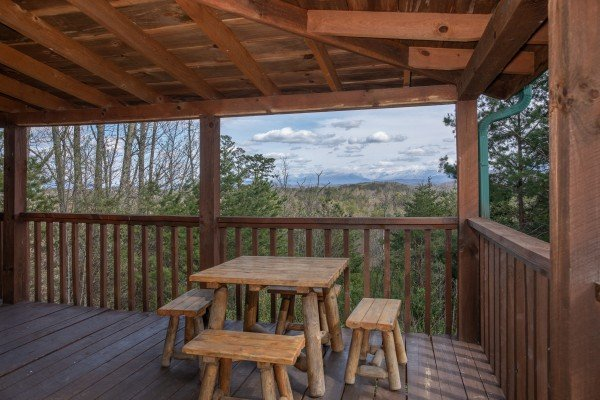 Outdoor dining space on the covered deck at Blue Mountain Views, a 1 bedroom cabin rental located in  Pigeon Forge