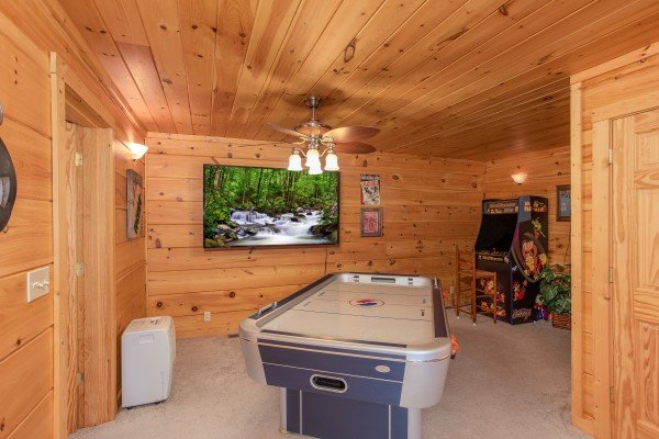 Air hockey table and large television in the game room at Awesome Views, a 4-bedroom cabin rental located in Pigeon Forge