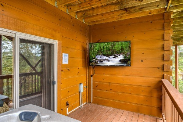 Wall mounted television near the hot tub at Awesome Views, a 4-bedroom cabin rental located in Pigeon Forge