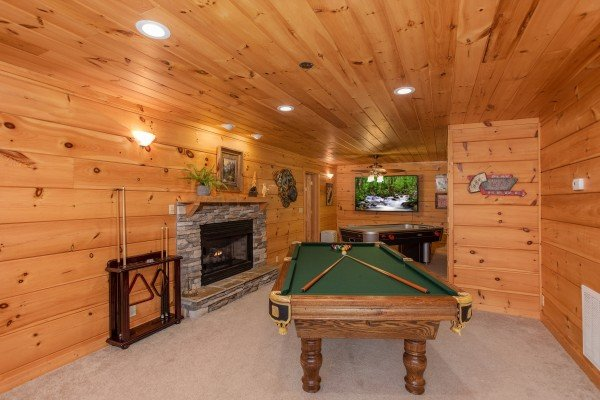 Pool table and stacked stone fireplace at Awesome Views, a 4-bedroom cabin rental located in Pigeon Forge
