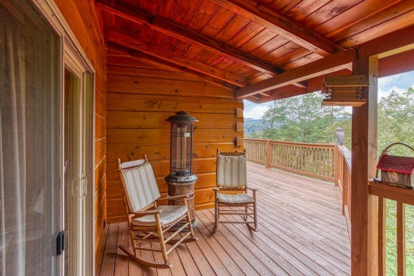 Rockers on a covered deck near a heater at Awesome Views, a 4-bedroom cabin rental located in Pigeon Forge