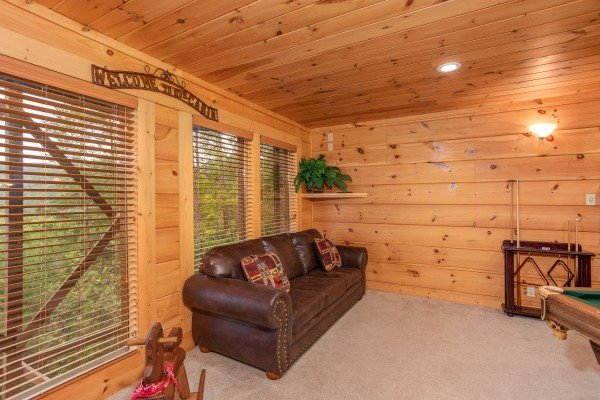 Sofa in the game room at Awesome Views, a 4-bedroom cabin rental located in Pigeon Forge