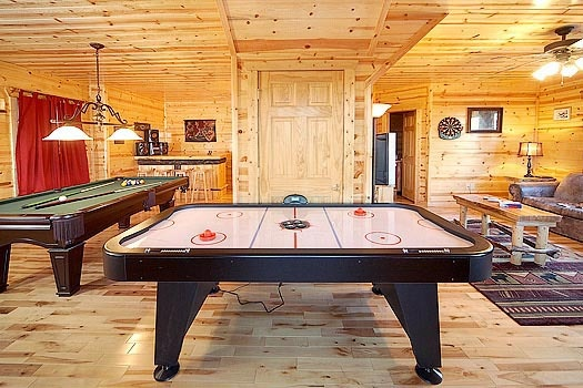 Game room with pool and air hockey tables at Bullwinkle's Place, a 1-bedroom cabin rental located in Gatlinburg