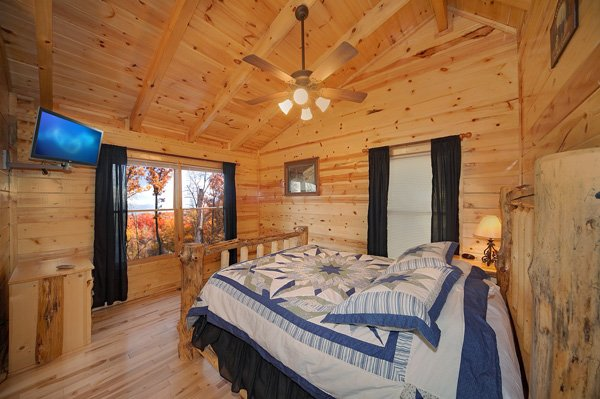Queen-sized log bed with wall-mounted television at Bullwinkle's Place, a 1-bedroom cabin rental located in Gatlinburg