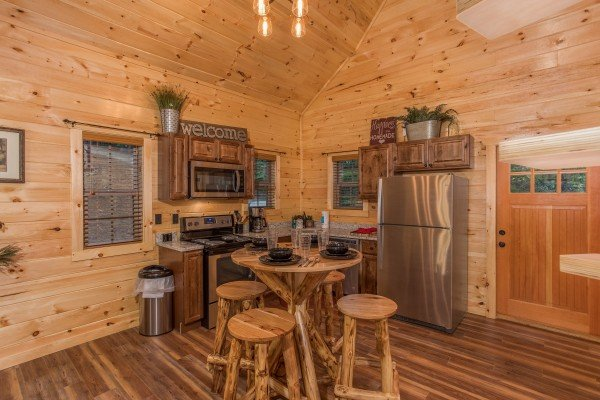 Dining table for four and kitchen with stainless appliances at Pigeon Forge Treehouse, a 1 bedroom cabin rental located in Pigeon Forge