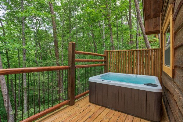 Hot tub with privacy fence on the deck at Pigeon Forge Treehouse, a 1 bedroom cabin rental located in Pigeon Forge