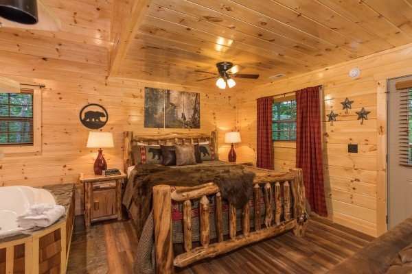 King log bed with two nightstands on the main floor at Pigeon Forge Treehouse, a 1 bedroom cabin rental located in Pigeon Forge