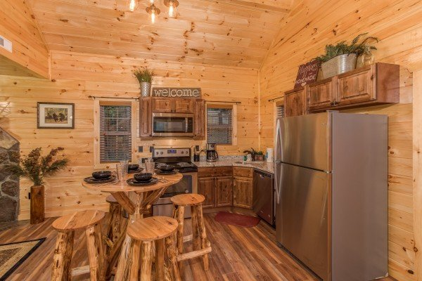 Kitchen with stainless appliances and dining table for four at Pigeon Forge Treehouse, a 1 bedroom cabin rental located in Pigeon Forge