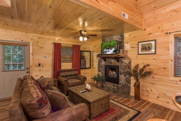 Living room with sofa, chair, fireplace, and TV at Pigeon Forge Treehouse, a 1 bedroom cabin rental located in Pigeon Forge
