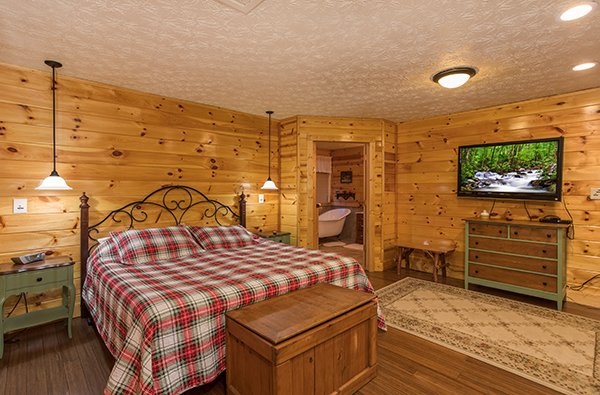 Queen bedroom with dresser, TV, and en suite at Rustic Ranch, a 2 bedroom cabin rental located in Pigeon Forge