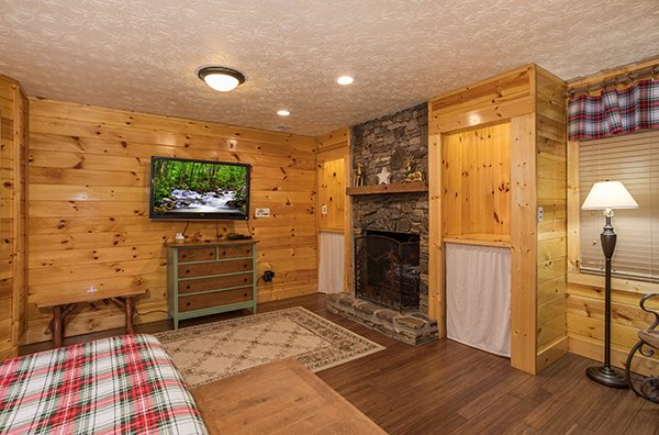 Fireplace and TV in a bedroom at Rustic Ranch, a 2 bedroom cabin rental located in Pigeon Forge
