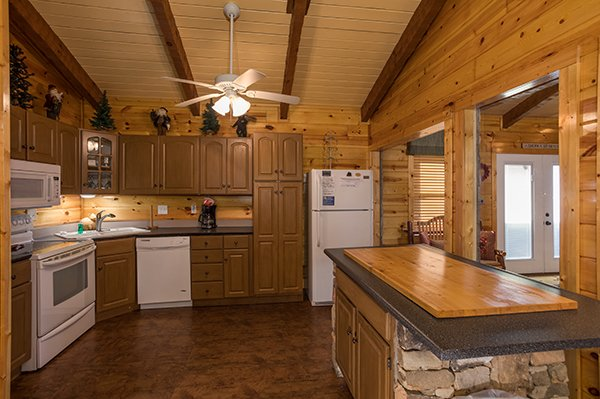 Kitchen with white appliances and an island at Rustic Ranch, a 2 bedroom cabin rental located in Pigeon Forge