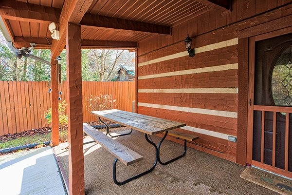 Picnic table under a covered deck at Rustic Ranch, a 2 bedroom cabin rental located in Pigeon Forge