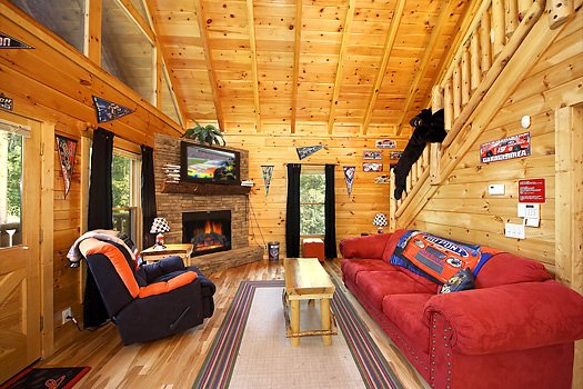 Living room with vaulted ceiling, fireplace, and TV at Nascar Nation, a 2 bedroom cabin rental located in Pigeon Forge