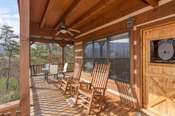 Rocking chairs and outdoor dining space for four on a covered deck at Oh The View, a 3-bedroom cabin rental located in Pigeon Forge