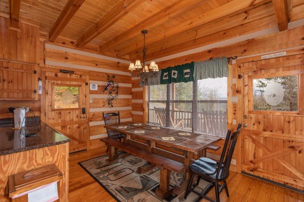 Dining table with two benches, two chairs, and seating for eight at Oh The View, a 3-bedroom cabin rental located in Pigeon Forge