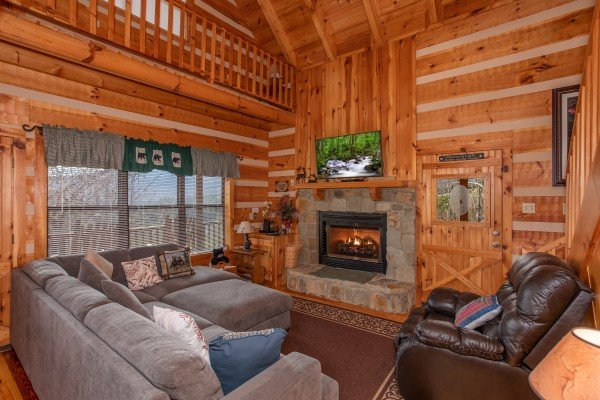 Living room with large sectional sofa, leather chair, fireplace, and TV at Oh The View, a 3-bedroom cabin rental located in Pigeon Forge