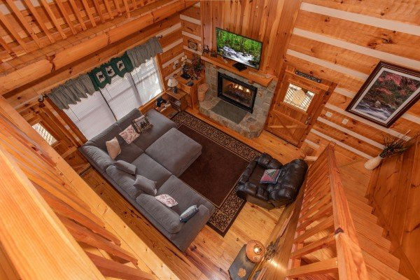 Looking down into the living room on the main floor from the upper floor at Oh The View, a 3-bedroom cabin rental located in Pigeon Forge