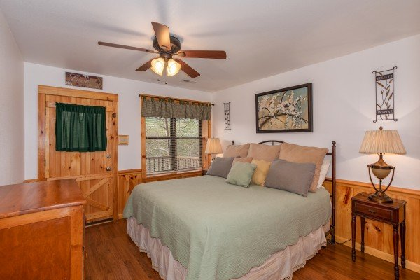 King-sized bed in a lower level bedroom with deck access at Oh The View, a 3-bedroom cabin rental located in Pigeon Forge