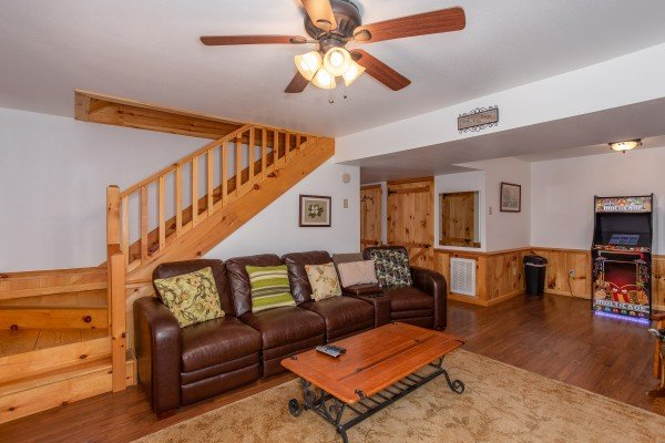 Living room with seating and an arcade game on the lower floor at Oh The View, a 3-bedroom cabin rental located in Pigeon Forge