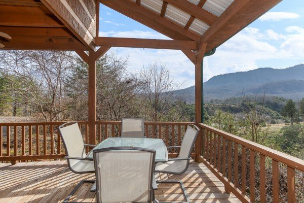 Outdoor dining space for four on a covered deck with mountain views at Oh The View, a 3-bedroom cabin rental located in Pigeon Forge