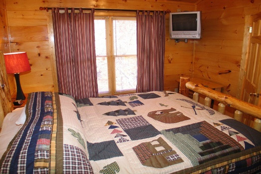 third floor bedroom with double windows and tv in corner at dragonfly a 2 bedroom cabin rental located in gatlinburg