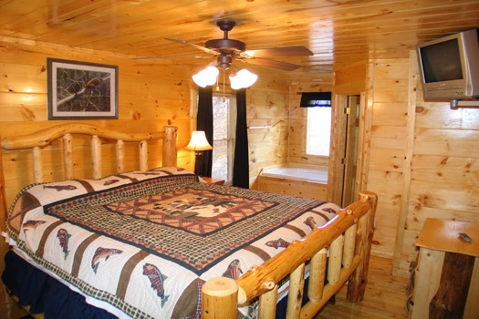 King log framed bed with jacuzzi tub in bedroom at Dragonfly, a 2-bedroom cabin rental located in Gatlinburg