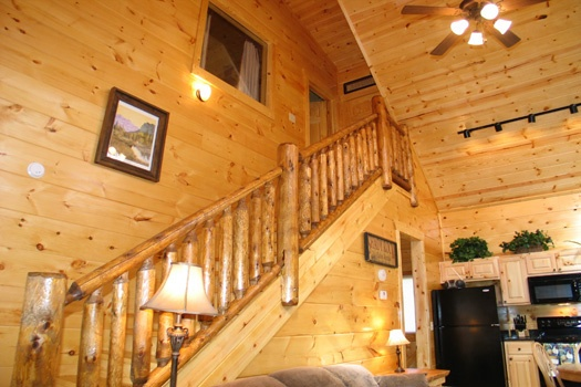 staircase with log banisters at dragonfly a 2 bedroom cabin rental located in gatlinburg