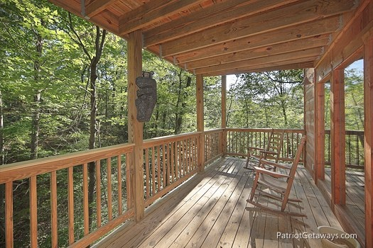 chairs sitting under a covered deck at a moment in time a 2 bedroom cabin rental located in gatlinburg