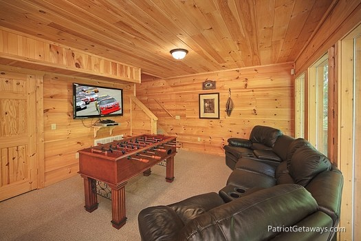 a large gameroom with sectional sofa seating and foosball table and tv at a moment in time a 2 bedroom cabin rental located in gatlinburg